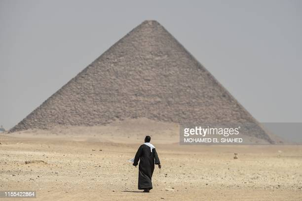 A man walks next to the Red Pyramid in Dahshur some 30 kilometres south of Cairo on July 13 2019 Egyptian archaeologists unveiled Saturday several...