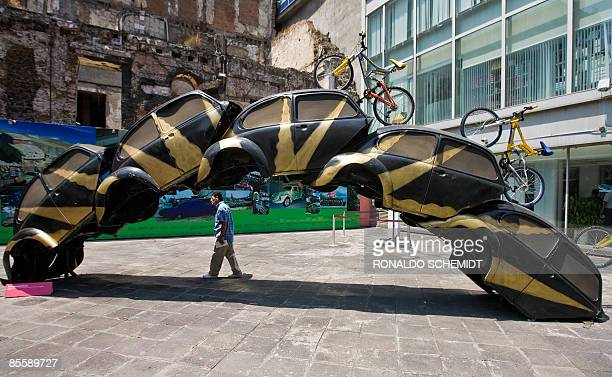 A man walks next to the sculpture Sobreponiendose part of the A vuelta de rueda exhibition of Mexican artist Betsabee Romero on March 24 2009 in the...