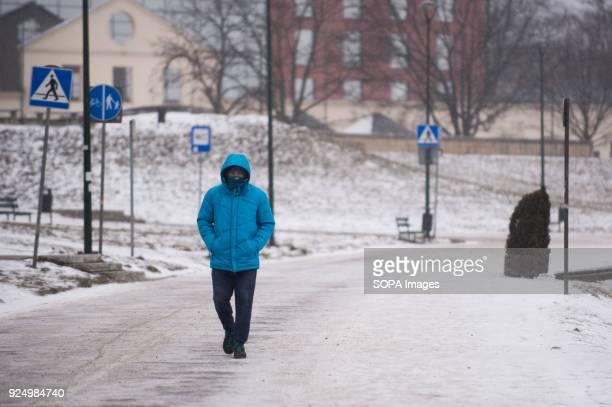A man walks next to Vistula river in Krakow during low temperature