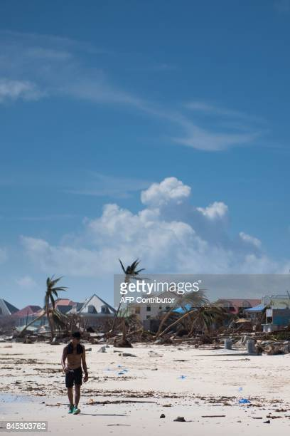 A man walks on a beach where houses and palm trees have been damaged by Irma hurricane on September 10 2017 in Orient Bay on the French Carribean...
