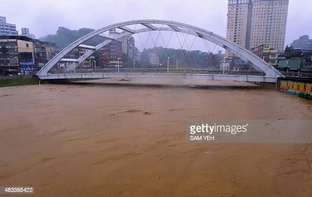 A man walks on a bridge above the Jingmei river as typhoon Soudelor hits Taipei on August 8 2015 Typhoon Soudelor battered Taiwan with fierce winds...