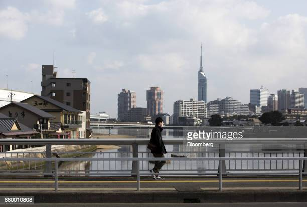 A man walks on a bridge as the Fukuoka Tower center right stands in the background amid commercial and residential buildings in Fukuoka Japan on...