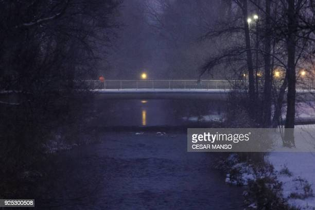 A man walks on a bridge during a snowfall in Burgos northern Spain on February 28 2018 School was cancelled across swathes of Europe as a blast of...