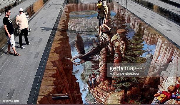 A man walks on a chalk 3D artwork by US artist Kurt Wenner on March 4 2015 near the Jumeirah Beach Residence in Dubai during the Canvas Festival a...