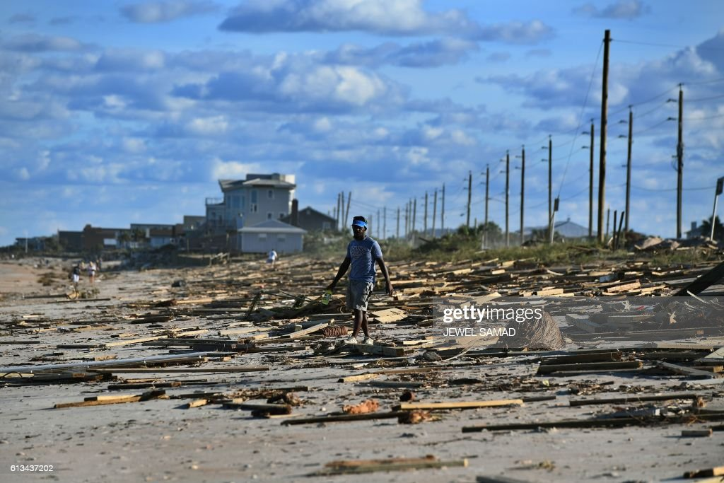 TOPSHOT - A man walks on a debris covered beach in St Augustine, Florida, on October 8, 2016, after Hurricane Matthew passed the area. Hurricane Matthew weakened to a Category 1 storm Saturday as it neared the end of a four-day rampage that left a trail of death and destruction across the Caribbean and up the US Atlantic coast. The full scale of the devastation in hurricane-hit rural Haiti became clear as the death toll surged past 400, three days after Hurricane Matthew leveled huge swaths of the country's south. PHOTO / Jewel SAMAD