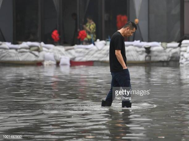Pedestrians walk on a flooded street caused by heavy rainstorms in Harbin city northeast China's Heilongjiang province 19 July 2018 Rainstorms...