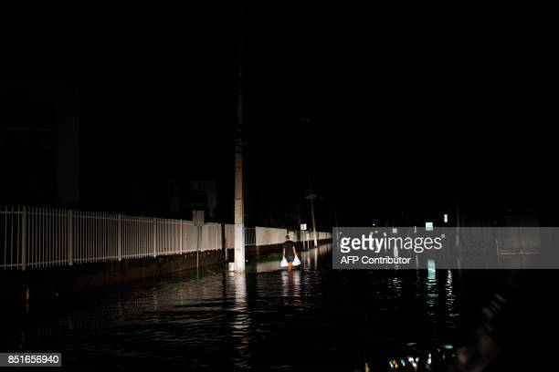 A man walks on a flooded street in the aftermath of Hurricane Maria in San Juan Puerto Rico late on September 21 2017 Puerto Rico has been battling...