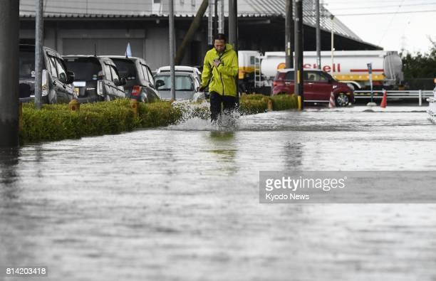 A man walks on a flooded street in the town of Oguchi on July 14 as heavy rain hit Aichi and Gifu prefectures in central Japan ==Kyodo