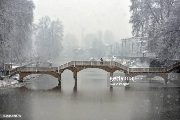 A man walks on a footbridge during heavy snowfall in Srinagar Indian administered Kashmir Fresh snowfall began in Kashmir valley breaking the intense...