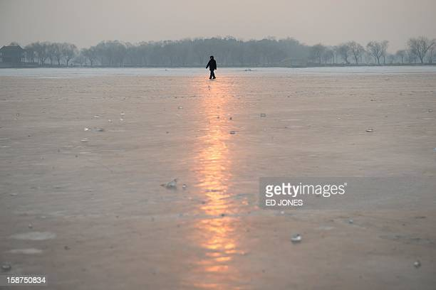 A man walks on a frozen lake at the Summer Palace in Beijing on December 27 2012 Forecasts were predicting temperatures of around minus 20 degrees in...