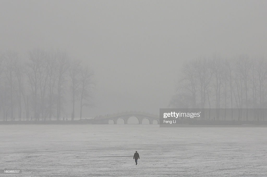 A man walks on a frozen lake during severe pollution on January 30, 2013 in Beijing, China. The fourth round of heavy smog to hit Beijing in one month has sent more people to the hospital with respiratory illnesses and prompted calls for legislation to curb pollution. The haze choking many Chinese cities covers a total area of 1.3 million square kilometers, the China's Ministry of Environmental Protection said Tuesday.