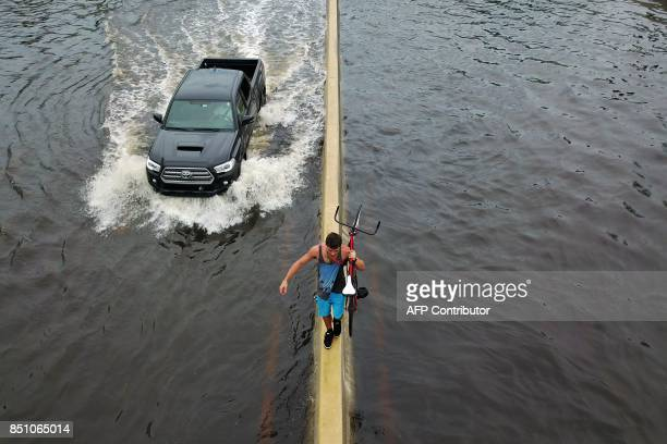 TOPSHOT A man walks on a highway divider while carrying his bicycle in the aftermath of Hurricane Maria in San Juan Puerto Rico Thursday September 21...