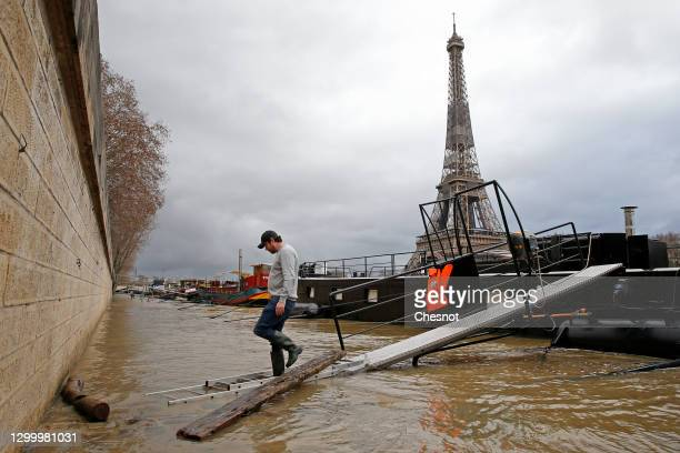 Man walks on a ladder surrounded by flood waters as he leaves his house boat near the Eiffel Tower on February 02, 2021 in Paris, France. Heavy rains...