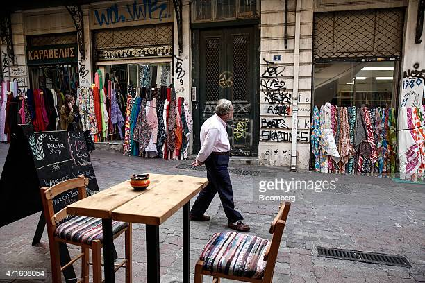 A man walks on a pedestrian street between a fabric store and a cafe in the Agia Irini district of Athens Greece on Saturday April 25 2015 The...