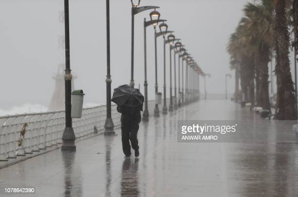 TOPSHOT A man walks on a rainy day on Beirut's deserted Manara seafront promenade on January 6 2019 as a fierce winter storm lashed the east coast of...
