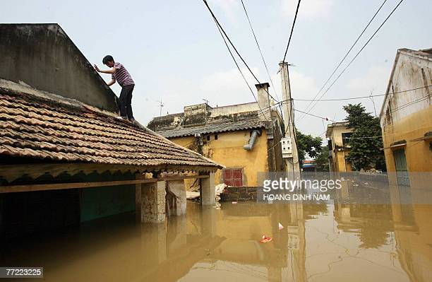 A man walks on a roof of a flooded house in Thach Thanh district in the central province of Thanh Hoa 08 October 2007 At least 58 people have died in...