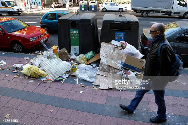 Man walks on a sidewalk lined with trash in Madrid, Spain. 11 days have passed since the cleaning strike began in Madrid. Dozens of streets remain...