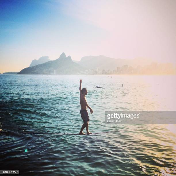 A man walks on a slackline across the ocean at Ipanema beach on June 8 2014 in Rio de Janeiro Brazil