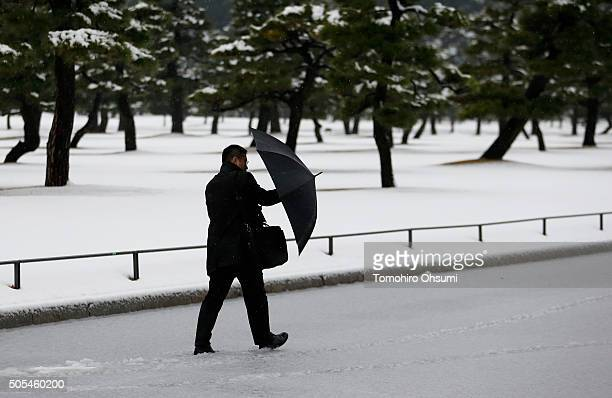 A man walks on a snow coverd road near the Imperial Palace on January 18 2016 in Tokyo Japan The first heavy snowfall of the season reached 6...
