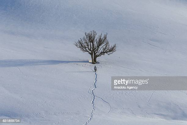 A man walks on a snow covered area in the Boyunpinar Neighborhood of Catak district in Van Turkey on January 17 2017 People living in Boyunpinar...
