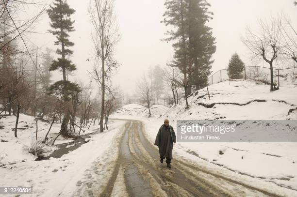 A man walks on a snow covered road on January 30 2018 in Tangmarg some 40 kilometers north of Srinagar India The sevenweek dry spell ended in Kashmir...