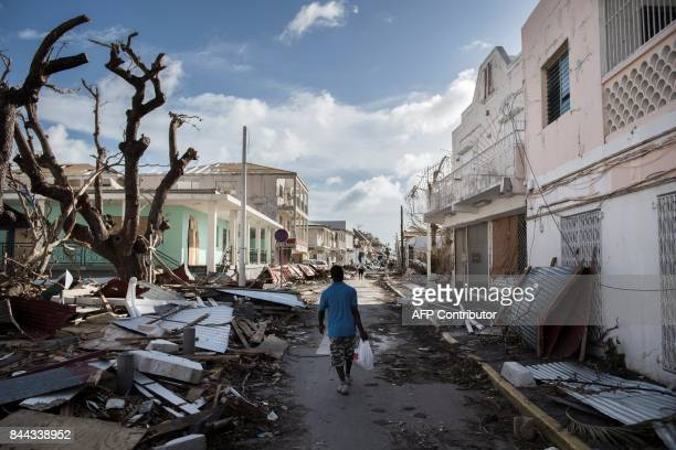 TOPSHOT A man walks on a street covered in debris after hurricane Irma hurricane passed on the French island of SaintMartin near Marigot on September...