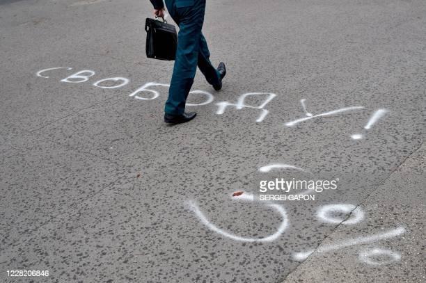 "Man walks on an asphalt yard painted with an inscription reading ""Freedom! 3%"", referring to Alexander Lukashenko, who has been nicknamed ""Sasha 3..."