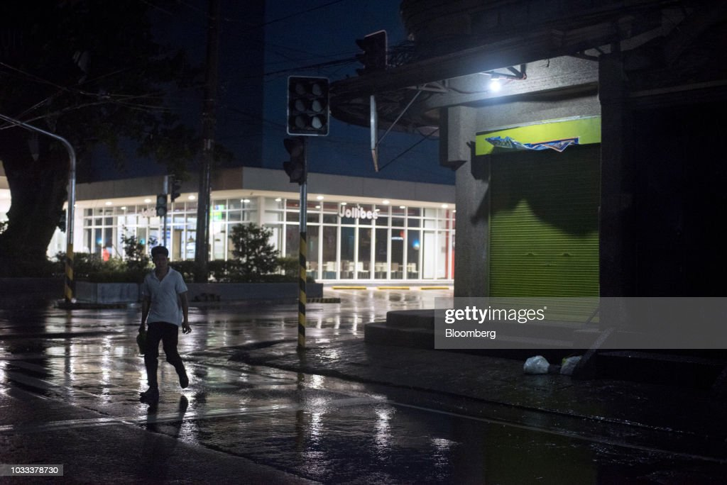 A man walks on an empty street ahead of Typhoon Mangkhut's arrival in Tuguegarao, Cagayan province, the Philippines, on Friday, Sept. 14, 2018. Super Typhoon Mangkhut is expected to threaten Chinas Guangdong coastline, and Hong Kong, with a possible direct strike that may cause as much as $120 billion in damage and economic losses. Photographer: Carlo Gabuco/Bloomberg via Getty Images