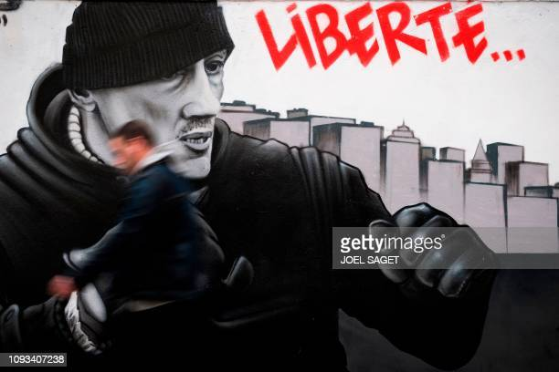 Man walks on February 3, 2019 in Paris, France, in front of a mural by the artist collective named Black Lines and depicting Christophe Dettinger,...