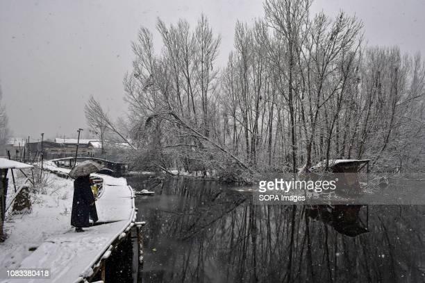 A man walks on foot bridge in the interiors of Dal Lake during heavy snowfall in Srinagar Indian administered Kashmir Fresh snowfall began in Kashmir...