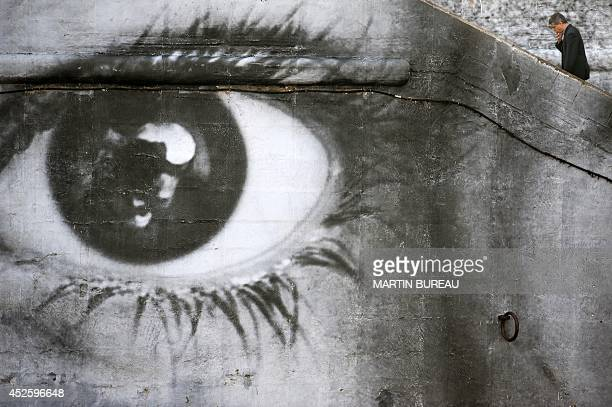A man walks on October 7 2009 by a giant photography by Belgian artist and photographer JR pasted on a wall of the bank of the River Seine as part of...