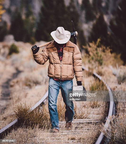 Man walks on railroad tracks carrying tools and looking down