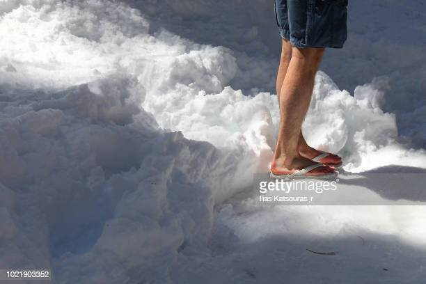 man walks on snow in shorts and flip-flops, cold weather - shorts stock pictures, royalty-free photos & images