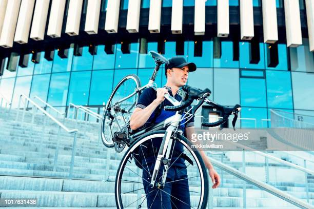 Man walks on stairs outside and holds on to his commuter bicycle