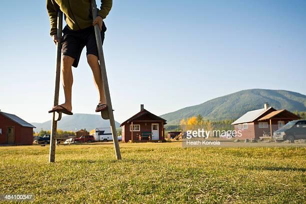 Man walks on stilts in rural setting.