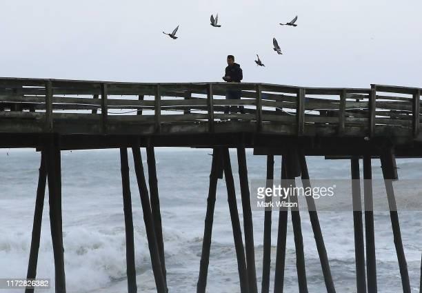 Man walks on the Avalon Pier that was damaged by Hurricane Dorian on September 6, 2019 in Kill Devil Hills, North Carolina. Dorian passed Charleston...