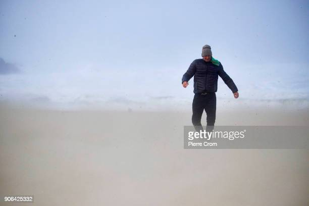 A man walks on the beach as a hurricaneforce storm is blowing galewinds of up to force 12 on January 18 2018 in The Hague Netherlands The Dutch...