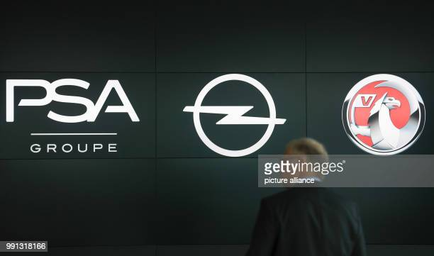 A man walks on the brink of a press conference by the company logos of Opel and PSA at the Opel Design Center in Ruesselsheim Germany 9 November 2017...