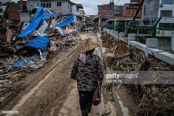 A man walks on the damaged road in the aftermath on July 12 2016 in Fuijan China Typhoon Nepartak hit China's coastal southeastern Fujian province...