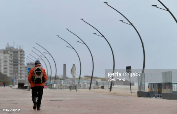 A man walks on the deserted boardwalk of Belgium's West Flanders city of Koksijde on March 20 2020 as a lockdown is in effect in the country to...