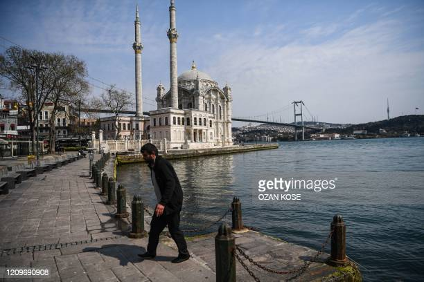 Man walks on the empty shore side of Ortakoy, as July 15 Martyrs' Bridge, known as the Bosphorus Bridge and Ortakoy mosque are seen in the backround...