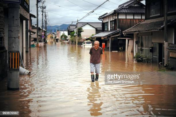 A man walks on the flooded road as the water level lowered in the submerged Mabicho area after Odagawa River banks collapse due to heavy rain on July...