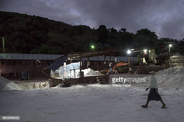 A man walks on the ground made of white marble dust in a ruby mine