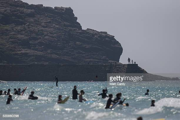 A man walks on the harbour wall as people swim and surf in the sea as they enjoy the fine weather at Sennen Cove on May 30 2016 in Cornwall England...