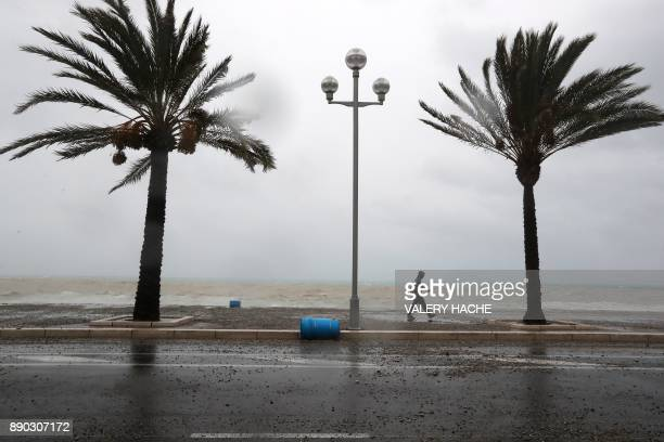 A man walks on the landmark Promenade des Anglais avenue as massive waves break against the shore in the French riviera city of Nice southeastern...