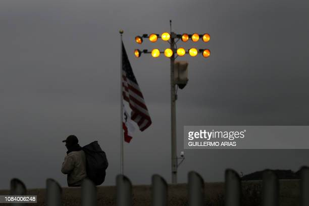 TOPSHOT A man walks on the Mexican side as a US flag flies near the USMexico border as seen from Tijuana Baja California state Mexico on January 17...