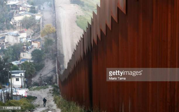 A man walks on the Mexican side of the USMexico border barrier on April 2 2019 in Tijuana Mexico US President Donald Trump told reporters last week...