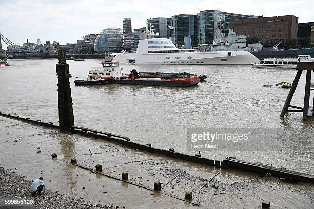 A man walks on the pebble shore as Russian billionaire Andrey Melnichenko's £225m Philippe Starckdesigned boat is seen moored next to HMS Belfast on...