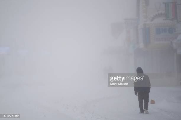 A man walks on the snow covered boardwalk during a snow storm on January 4 2018 in Atlantic City New Jersey A 'bomb cyclone' winter storm has caused...
