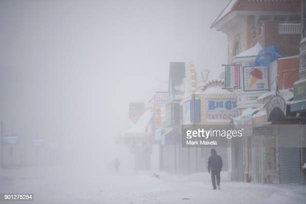 A man walks on the snow covered boardwalk during a snow storm on January 4 2018 in Atlantic City New Jersey A bomb cyclone winter storm has caused...